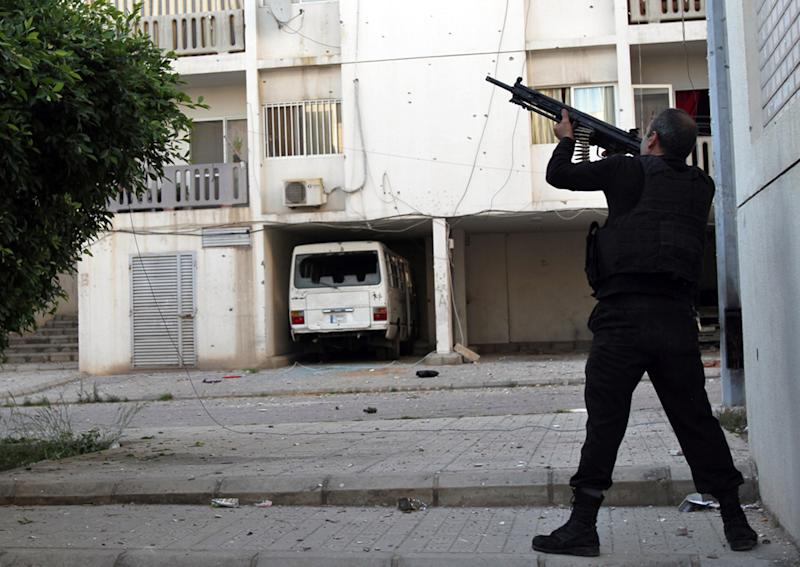A Sunni gunman fires his machine gun during clashes that erupted between pro and anti-Syrian regime gunmen, in the northern port city of Tripoli, Lebanon, Thursday, May. 23, 2013. Opponents and supporters of Syrian President Bashar Assad traded heavy machine gun fire and mortar shells in the Lebanese port city of Tripoli, leaving five people dead in what was described as some of the heaviest fighting there in years, officials said Thursday. (AP Photo)