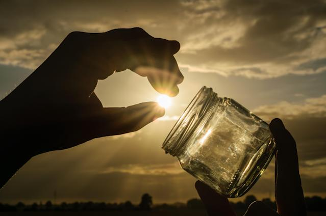 Person holding a jar against a sunny sky.