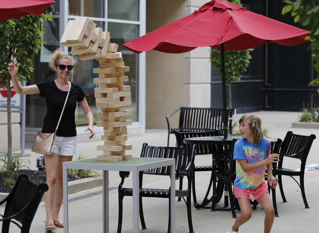IMAGE DISTRIBUTED FOR WASHINGTON PRIME GROUP - Veneta Bodurova, left, and her daughter Emma, from Delaware, Ohio, play a game of giant Jenga during the grand opening of The Yard at Polaris Fashion Place Sunday, July 15, 2018 in Columbus, Ohio. The Yard is Polaris Fashion Place's newest community gathering place where people can enjoy outdoor games while shopping and dining. (Jay LaPrete/AP Images for Washington Prime Group)