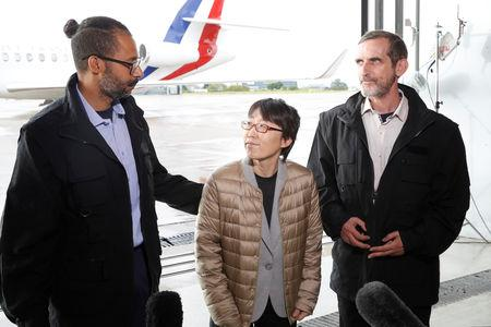 Freed French hostages Patrick Picque and Laurent Lassimouillas stand next to a South Korean hostage as they talk to the media upon their arrival at the Villacoublay airport, in Velizy-Villacoublay, France May 11, 2019. Francois Guillot/Pool via REUTERS