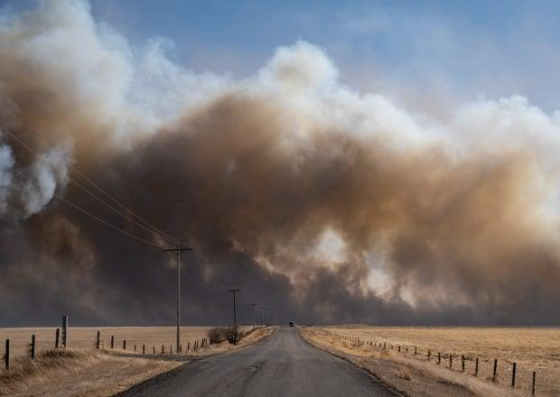 This image, taken by Kyle Brittain of The Weather Network, shows smoke billowing in southern Alberta. A massive grass fire has forced the evacuation of the village of Carmangay. (Kyle Brittain/The Weather Network - image credit)