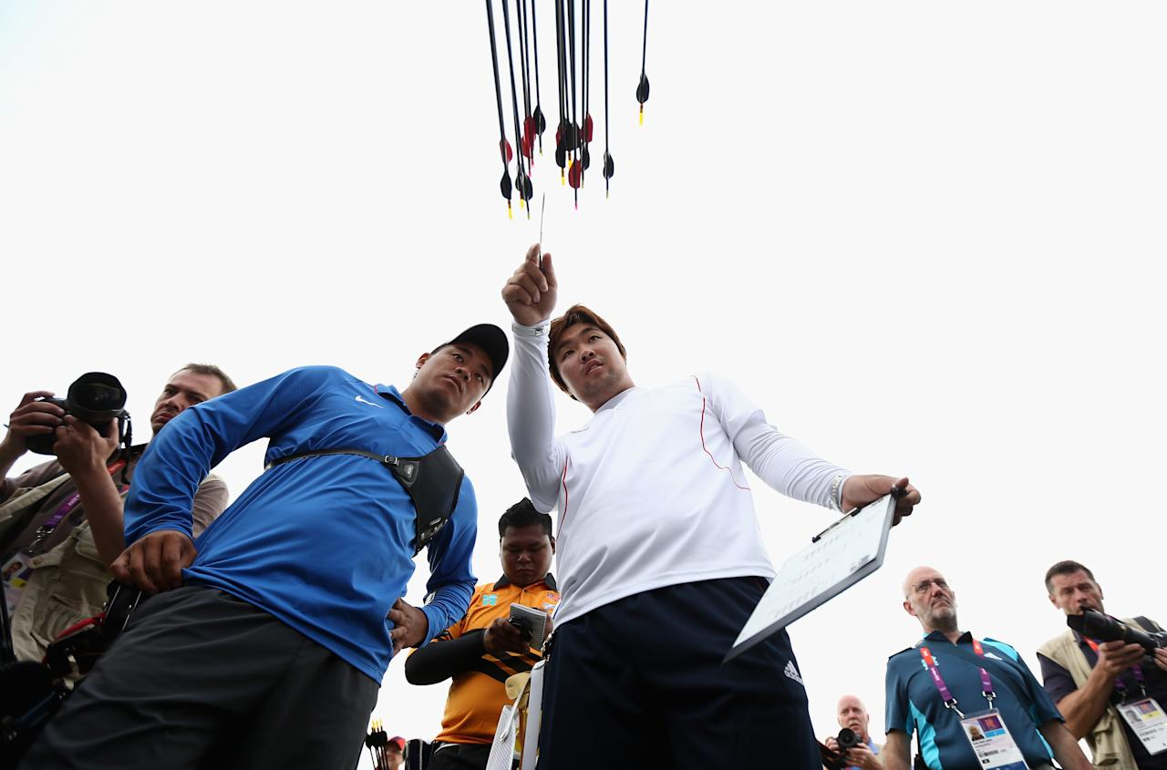 Im Dong Hyun (R) of Korea inspects the target after breaking the World Record during the Men's Individual Archery Ranking Round on Olympics Opening Day as part of the London 2012 Olympic Games at the Lord's Cricket Ground on July 27, 2012 in London, England.  (Photo by Paul Gilham/Getty Images)