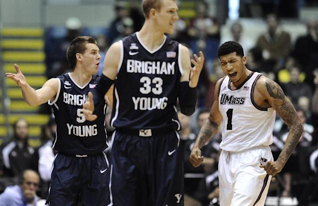 BYU's Kyle Collinsworth, left, and Nate Austin, center, and Massachusetts' Maxie Esho, right, gesture after an official's call during the second half of an NCAA college basketball game, Saturday, Dec. 7, 2013, in Springfield, Mass. Massachusetts won 105-96. (AP Photo/Jessica Hill)