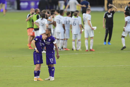 Orlando City forward Chris Mueller (9) and forward Nani (17) hug as the New England Revolution celebrate after an MLS playoff soccer match, Sunday, Nov. 29, 2020, in Orlando, Fla. (AP Photo/Matt Stamey)