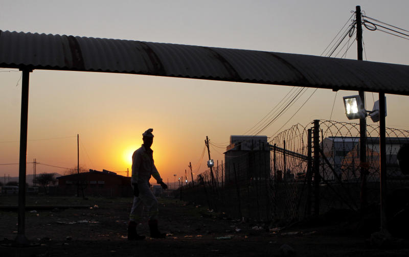 A miner from the Lonmin Platinum mine returns to work after Lonmin resolved a five-week strike by agreeing to pay raises of up to 22 percent, in Marikana, Rustenburg, South Africa, Thursday, Sept. 20, 2012. (AP Photo/Denis Farrell)