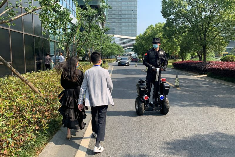 Security guard wearing thermal glasses developed by Chinese company Rokid patrols in Hangzhou