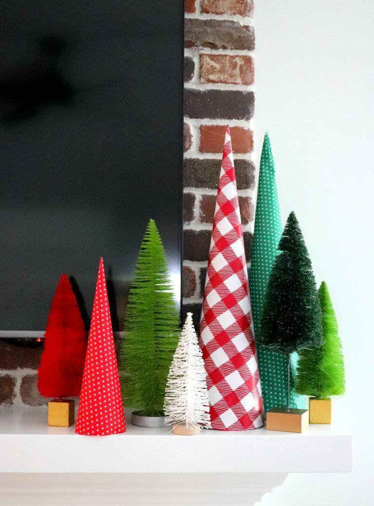 """<p>If you have leftover wrapping paper scraps, you can easily wrap them around a <a href=""""https://www.amazon.com/Darice-Paper-Mache-Cone-inches/dp/B00D32XA22?tag=syn-yahoo-20&ascsubtag=%5Bartid%7C10055.g.2996%5Bsrc%7Cyahoo-us"""" rel=""""nofollow noopener"""" target=""""_blank"""" data-ylk=""""slk:cardboard cone"""" class=""""link rapid-noclick-resp"""">cardboard cone</a> for some extra décor to mix in with your bottle brush trees. </p><p><em><a href=""""https://www.agirlandagluegun.com/2018/12/how-to-make-a-paper-cone-christmas-tree-for-cheap.html"""" rel=""""nofollow noopener"""" target=""""_blank"""" data-ylk=""""slk:Get the tutorial at a Girl and a Glue Gun »"""" class=""""link rapid-noclick-resp"""">Get the tutorial at a Girl and a Glue Gun »</a></em></p>"""