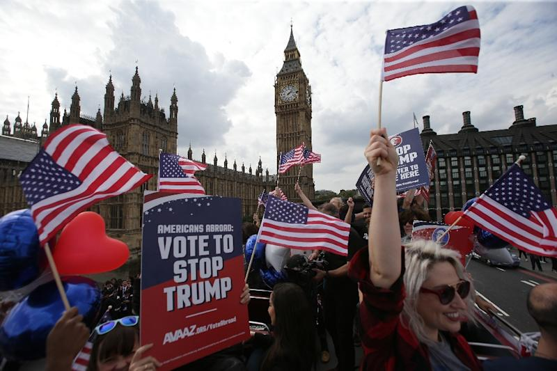"""Activists wave US flags as they ride a """"Stop Trump"""" bus in London on September 21, 2016 (AFP Photo/Daniel Leal-Olivas)"""