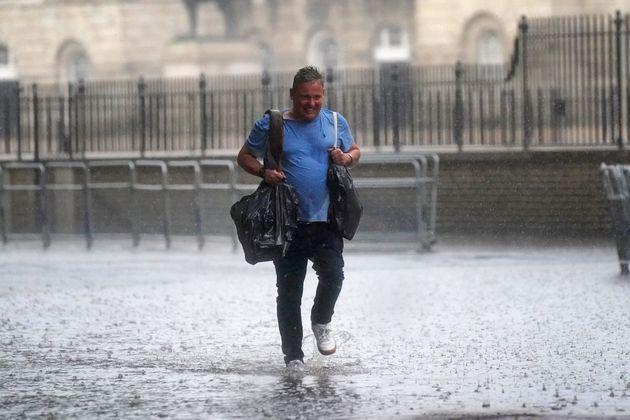 A man walks through water in Horse Guards Road on July 25 (Photo: Victoria Jones - PA Images via Getty Images)