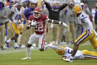 Arkansas running back Trelon Smith (22) slips past LSU defenders Jay Ward (5) and Todd Harris Jr. (4) as he runs the ball during the second half of an NCAA college football game Saturday, Nov. 21, 2020, in Fayetteville, Ark. (AP Photo/Michael Woods)