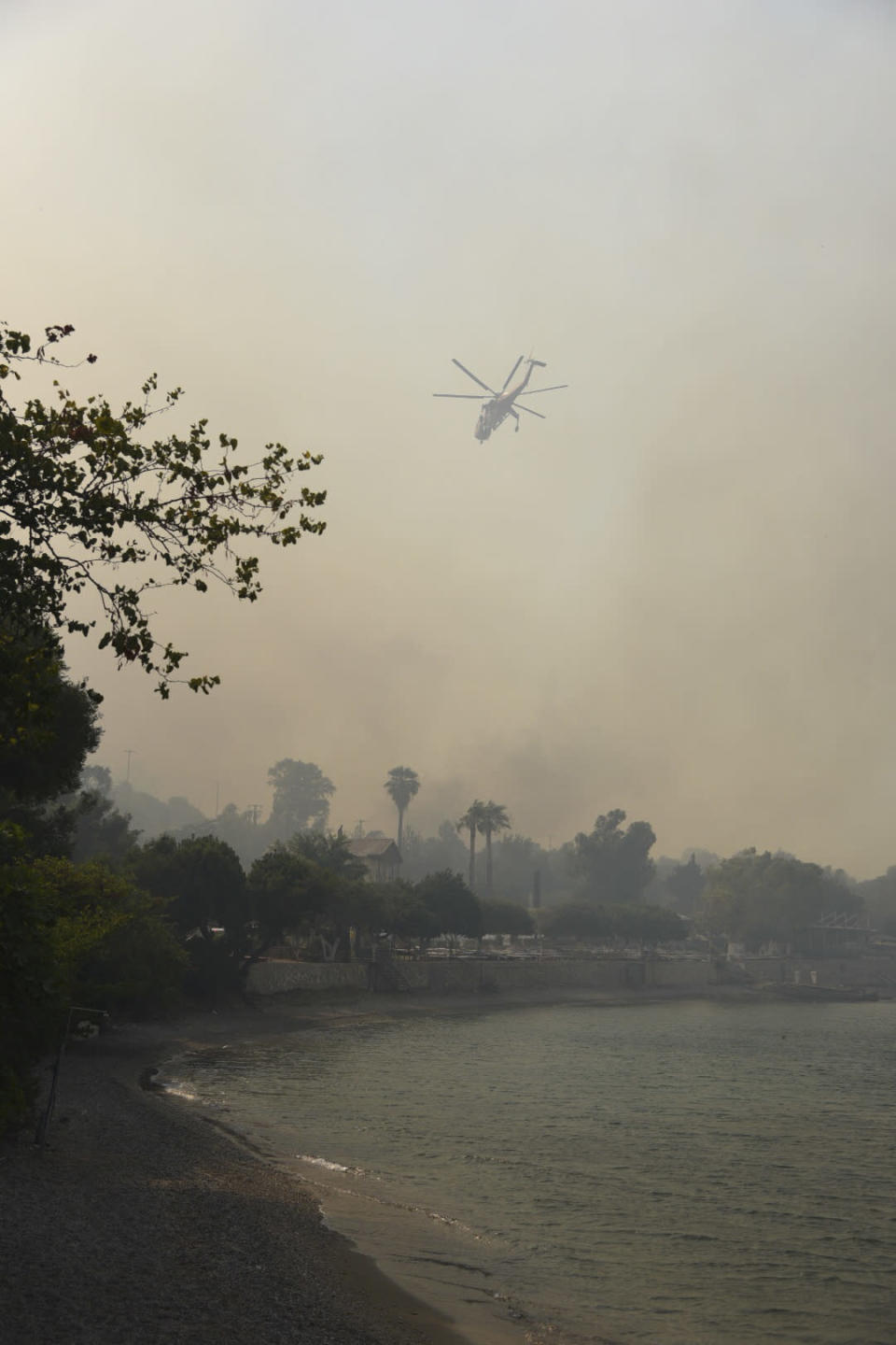 A helicopter operates during a wildfire near Ziria village, west of Patras, Greece, Saturday, Jul. 31, 2021. The fire, which started high up on a mountain slope, has moved dangerously close to seaside towns and the Fire Service has send a boat to help in a possible evacuation of people. (AP Photo/Andreas Alexopoulos)