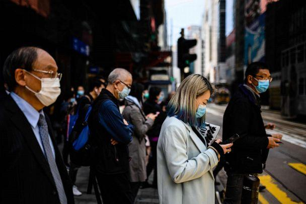 PHOTO: Pedestrians wear face masks as they walk on a footbridge in Hong Kong on Feb. 12, 2020. (Anthony Wallace/AFP via Getty Images)