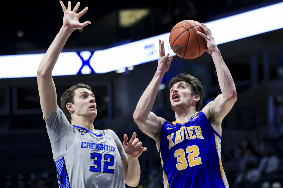 Creighton center Ryan Kalkbrenner, left, defends as Xavier forward Zach Freemantle drives to the basket in the first half of an NCAA college basketball game, Saturday, Feb. 27, 2021, in Cincinnati. (AP Photo/Aaron Doster)