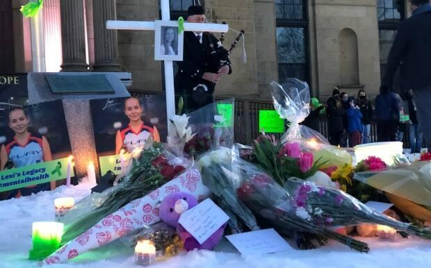 Flowers, teddy bears, and pictures of Lexi Daken that were left outside the provincial legislature during a vigil Feb. 28.