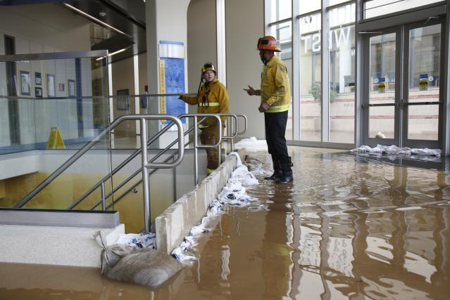 Firefighters talk after damming up a stairway inside UCLA's Pauley Pavilion sporting arena as water flows from a broken thirty inch water main that was gushing water onto Sunset Boulevard near the UCLA campus in the Westwood section of Los Angeles July 29, 2014. The geyser from the 100-year old water main flooded parts of the campus and stranded motorists on surrounding streets. REUTERS/Danny Moloshok (UNITED STATES - Tags: DISASTER ENVIRONMENT)