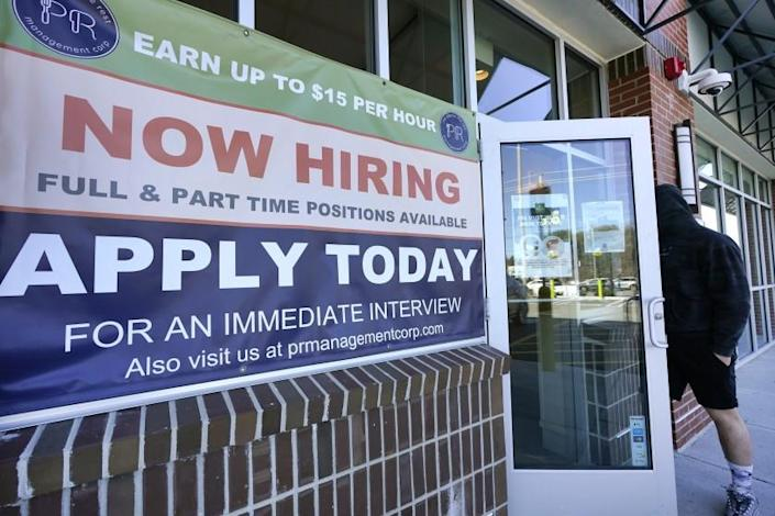 """A man walks into a restaurant displaying a """"Now Hiring"""" sign, Thursday, March 4, 2021, in Salem, N.H. U.S. employers added a robust 379,000 jobs last month, the most since October and a sign that the economy is strengthening as confirmed viral cases drop, consumers spend more and states and cities ease business restrictions. (AP Photo/Elise Amendola)"""
