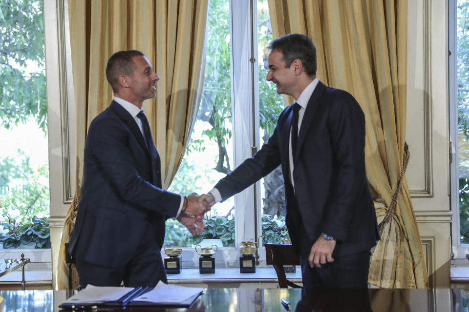 Greece's Prime Minister Kyriakos Mitsotakis, right, shakes hands with UEFA President Aleskander Ceferin, during their meeting in Athens, Tuesday, Feb. 25, 2020. Mitsotakis requested UEFA's help to clean up Greek soccer last month and has said he was willing to request expulsion of Greece's teams from European competition and even suspend the league unless major clubs sign up to a reform plan aimed stamping out match-related violence and widespread allegations of corruption in the sport. (AP Photo/Petros Giannakouris)