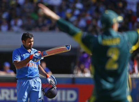 India's Sharma celebrates reaching his century as Australia's Bailey reacts during their one day international tri-series cricket match at the Melbourne Cricket Ground