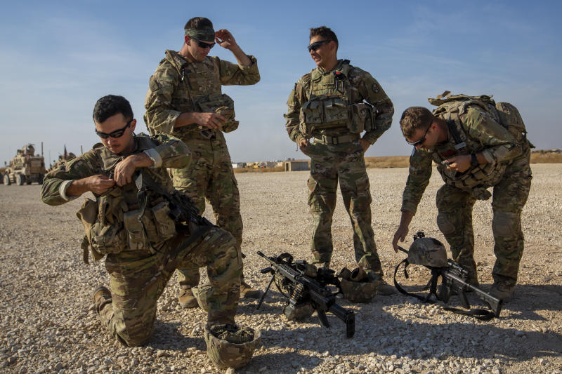Crewmen rest their weapons after training with Bradley fighting vehicles at a US military base at undisclosed location in Northeastern Syria, Monday, Nov. 11, 2019. The deployment of the mechanized force comes after US troops withdrew from northeastern Syria, making way for a Turkish offensive that began last month. (AP Photo/Darko Bandic)