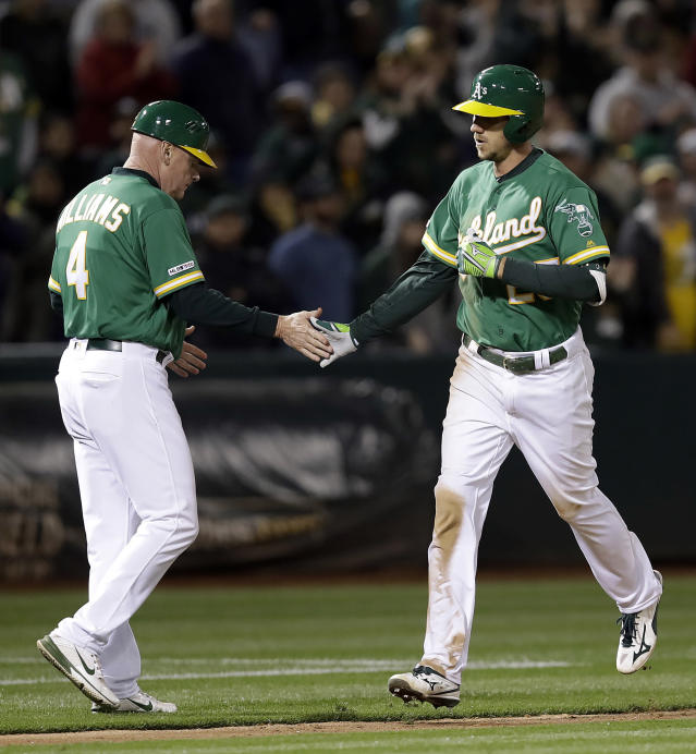 Oakland Athletics' Stephen Piscotty, right, is congratulated by third base coach Matt Williams after hitting a home run off Seattle Mariners' Connor Sadzeck during the eighth inning of a baseball game Friday, May 24, 2019, in Oakland, Calif. (AP Photo/Ben Margot)