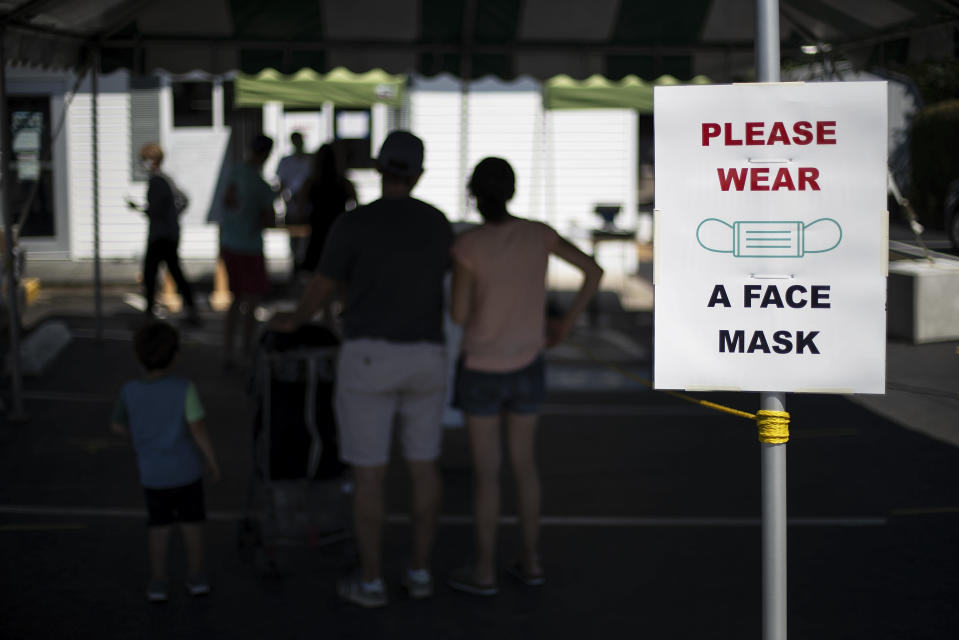 Customers with masks line up at a Brickley's Ice Cream shop, one of two stores, in Narragansett, R.I., Wednesday, July 29, 2020. The other nearby location closed when teenage workers were harassed by customers who refused to wear a mask or socially distance. Disputes over masks and mask mandates are playing out at businesses, on public transportation and in public places across America and other nations. (AP Photo/David Goldman)