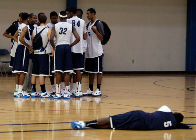 FILE - In this June 12, 2011, file photo, a player lies on the court as others huddle up at the Nike Elite 100 basketball camp in St. Louis. The Commission on College Basketball sharply directed the NCAA to take control of the sport, calling for sweeping reforms to separate pro and college tracks, permit players to return to school after going undrafted by the NBA and ban cheating coaches for life. The commission offered harsh assessments of toothless NCAA enforcement, as well as the shady summer basketball circuit that includes AAU leagues and brings together agents, apparel companies and coaches looking to profit on teenage prodigies. (AP Photo/Tom Gannam, File)