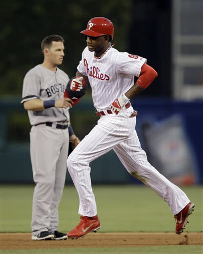 Philadelphia Phillies' Domonic Brown, right, rounds the bases past Boston Red Sox shortstop Stephen Drew after hitting a home run in the fourth inning of a baseball game, Wednesday, May 29, 2013, in Philadelphia. (AP Photo/Matt Slocum)