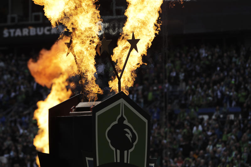 Fire effects go off behind two stars signifying the Seattle Sounders' two MLS Cup championship victories at the start of their season-opening MLS soccer match against the Chicago Fire, Sunday, March 1, 2020, in Seattle. The Sounders won the MLS Cup in 2016 and 2019. (AP Photo/Ted S. Warren)