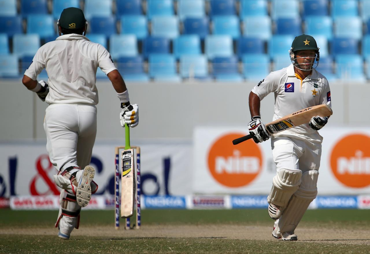 Batsmen Asad Shafiq (R) and Musbah Ul Haq of Pakistan run between wickets during the fourth day of the second Test cricket match between Pakistan and South Africa in Dubai on October 26, 2013. AFP PHOTO/MARWAN NAAMANI        (Photo credit should read MARWAN NAAMANI/AFP/Getty Images)