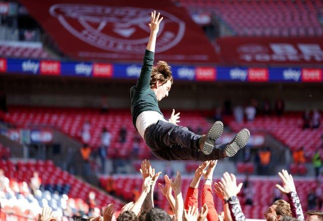 Brentford manager Thomas Frank is tossed into the air by his players