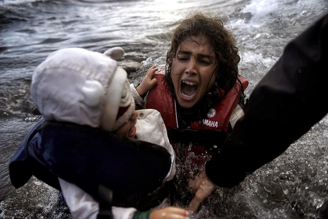 A woman falls into the water with her child as they disembark off a dinghi as refugees and migrants arrive at the Greek island of Lesbos after crossing the Aegean sea from Turkey, on October 2, 2015.