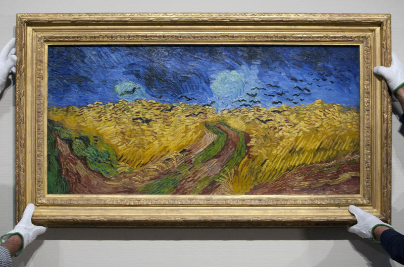 """Curators remove Vincent van Gogh's painting """"Wheatfield with Crows,"""" from the wall of the Van Gogh Museum in Amsterdam, Netherlands, Sunday, Sept. 23, 2012. While the museum closes for seven months for renovations, 75 works by the Dutch painter will be displayed instead across town at The Hermitage, an Amsterdam satellite of the Russian state museum. The tricky process of transporting the artworks under police escort began immediately after the last visitors left the museum Sunday evening and carried on through the night into Monday morning. The Van Gogh Museum reopens April 25, 2013. (AP Photo/Cris Toala Olivares)"""
