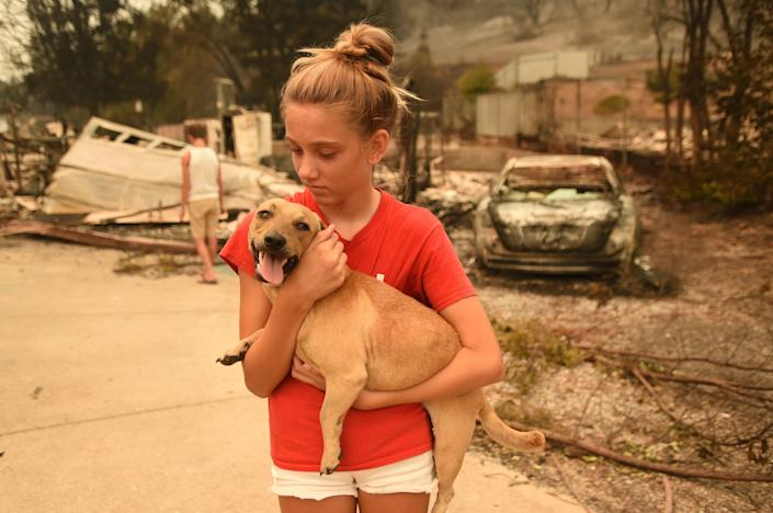 Kambryn Brilz, 12, holds her dog Zoe in front of what remains of her burnt home after she was returned safely by a neighbor during the Carr Fire.