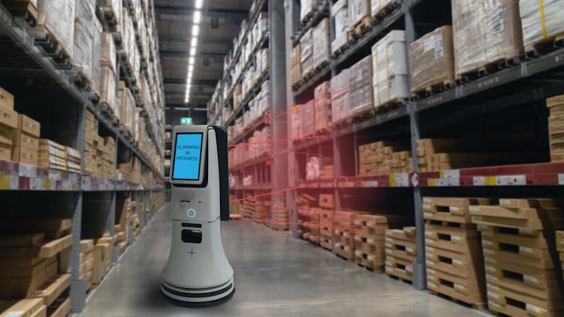 A device in the aisle between two warehouse racks reads RFID tags on the inventory.