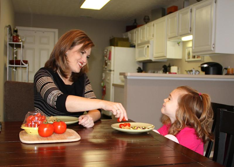 This Jan. 21, 2014 photo released by MediaSource shows Shannon McCormick, left, serving a tomato to her 4 year old daughter Sophie Chapman at their home in Gahanna, Ohio. Although not fond of tomatoes, McCormick keeps that fact from her daughter, who loves them. (AP Photo/MediaSource, Robert Leitch)