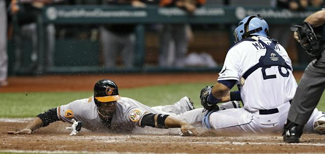 Tampa Bay Rays catcher Jose Molina (28) blocks home plate as Baltimore Orioles' Alexi Casilla attempts to score on a seventh-inning single by Nick Markakis off Rays relief pitcher Jake McGee during a baseball game Monday, Sept. 23, 2013, in St. Petersburg, Fla. Casilla was out. (AP Photo/Chris O'Meara)