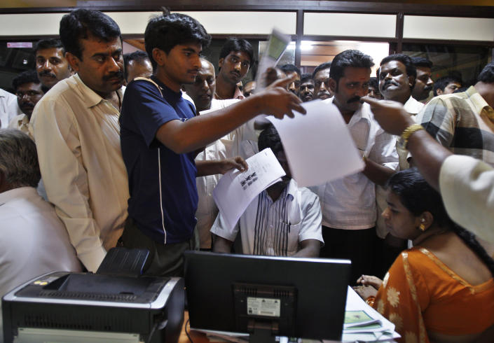 In this Dec. 10, 2012 photo, people crowd inside the government registrar's office to get their land registered, in Hoskote 30 kilometers (19 miles) from Bangalore in the southern Indian state of Karnataka. For years, Karnataka's land records were a quagmire of disputed, forged documents maintained by thousands of tyrannical bureaucrats who demanded bribes to do their jobs. In 2002, there were hopes that this was about to change. (AP Photo/Aijaz Rahi)