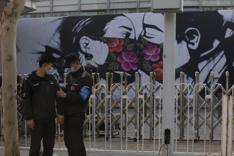 Chinese security personnel stand on duty near an art work outside the United States Embassy in Beijing on April 6, 2021. China accused the U.S. of causing humanitarian disasters through foreign military interventions in a report Friday, April 9, 2021 that was the latest broadside by Beijing amid increasingly contentious relations with the Biden administration. (AP Photo/Ng Han Guan)