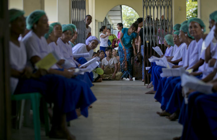 """In this Oct. 22, 2013 photo, men and women suffering from blindness hold their diagnosis papers in-hand as they wait to enter an operation theater to follow a simple surgical procedure to remove cataracts, as their relatives, center, wait outside at a government hospital in Bago, Myanmar. The veil of darkness is starting to lift, thanks to an """"assembly line"""" surgical procedure that allows cataracts to be removed safely, without stitches, through two small incisions, a technique pioneered by Nepalese master surgeon Sandut Ruit.(AP Photo/Gemunu Amarasinghe)"""