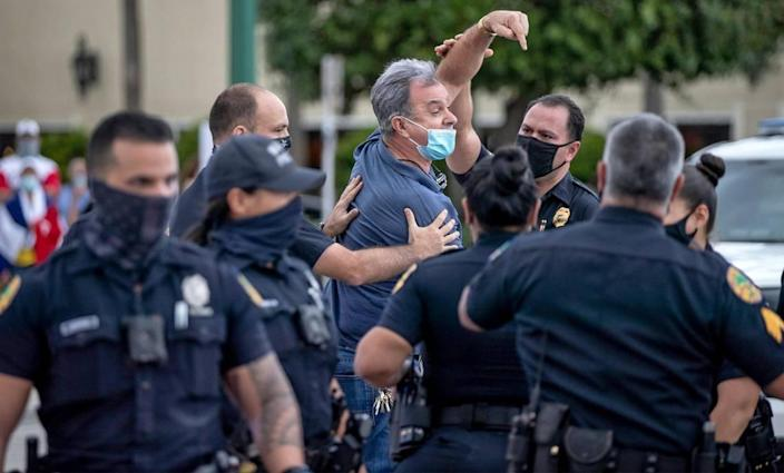 Ramon Saul Sanchez appears to be detained but then released by Miami Police during rally at Versailles Restaurant in Miami in support of Cuban artists arrested by the Cuban government on Saturday, November 28, 2020.