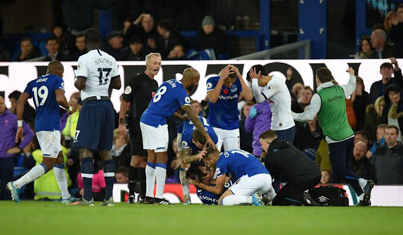 Teammates comfort Everton's Portuguese midfielder André Gomes (C floor) as he gets attention for an injury during the English Premier League football match between Everton and Tottenham Hotspur at Goodison Park in Liverpool, north west England on November 3, 2019. (Photo by Oli SCARFF / AFP) / RESTRICTED TO EDITORIAL USE. No use with unauthorized audio, video, data, fixture lists, club/league logos or 'live' services. Online in-match use limited to 120 images. An additional 40 images may be used in extra time. No video emulation. Social media in-match use limited to 120 images. An additional 40 images may be used in extra time. No use in betting publications, games or single club/league/player publications. / (Photo by OLI SCARFF/AFP via Getty Images)