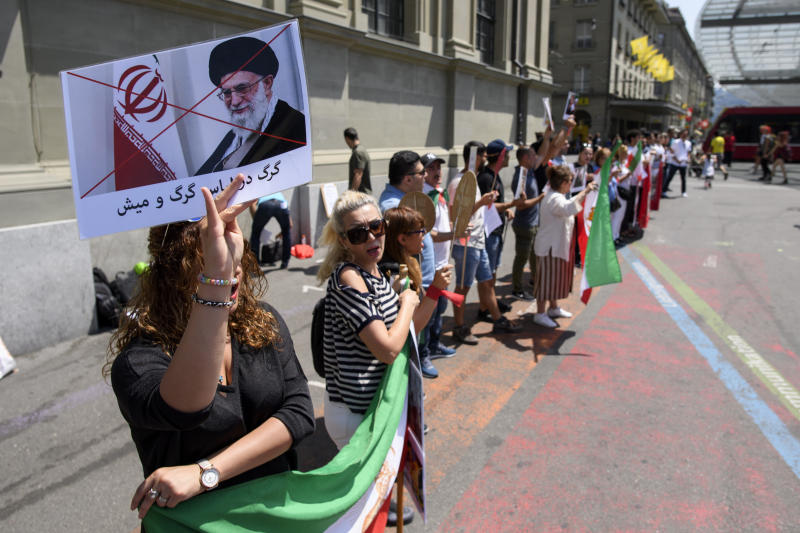 People demonstrate against the arrival of Iranian President Hassan Rohani in Bern, Switzerland, Monday, July 2, 2018. The Iranian President Hassan Rohani will be in Switzerland for a two days state visit. (Anthony Anex/Keystone via AP)