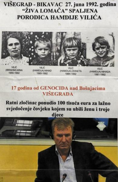Hamdija Vilic, a Bosnian Muslim and survivor of the 1992 massacres in Visegrad, is pictured during his deposition at the war crimes court sitting in front of a poster of his wife and three children, who were killed in the massacre