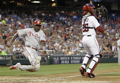 Philadelphia Phillies' John Mayberry (15) slides into the plate to score on a single by Cliff Lee as Washington Nationals catcher Jesus Flores looks for the throw in the fourth inning of a baseball game Tuesday, July 31, 2012, in Washington. (AP Photo/Carolyn Kaster)