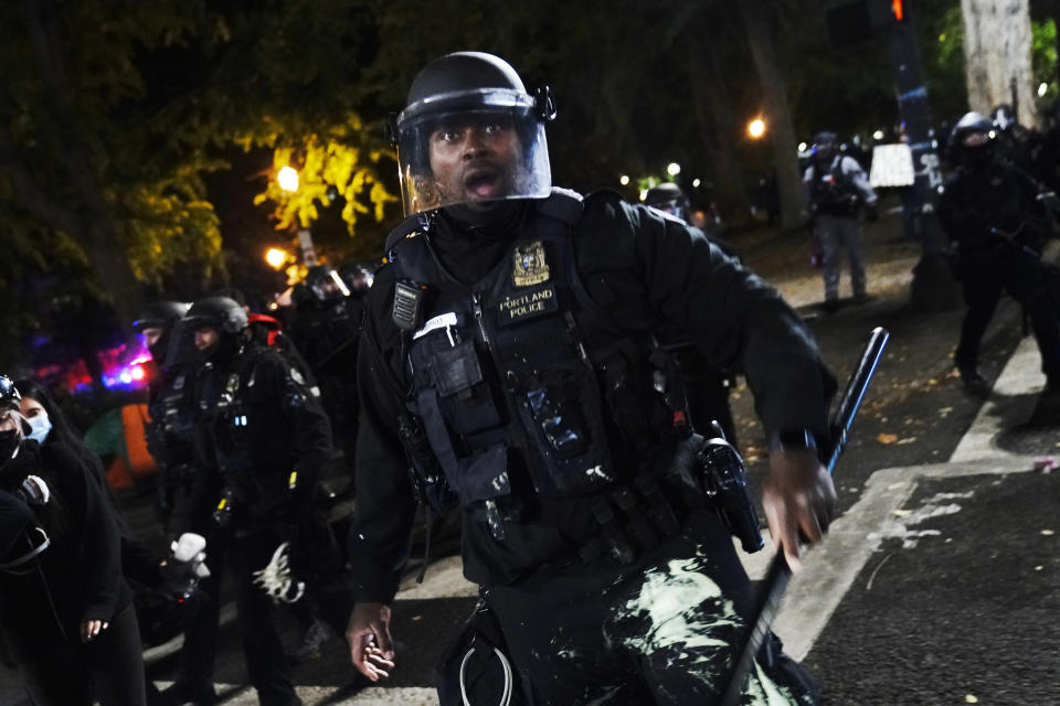 A Portland police officer pushes back protesters, Saturday, Sept. 26, 2020, in Portland. The protests, which began over the killing of George Floyd, often result frequent clashes between protesters and law enforcement. (AP Photo/John Locher)