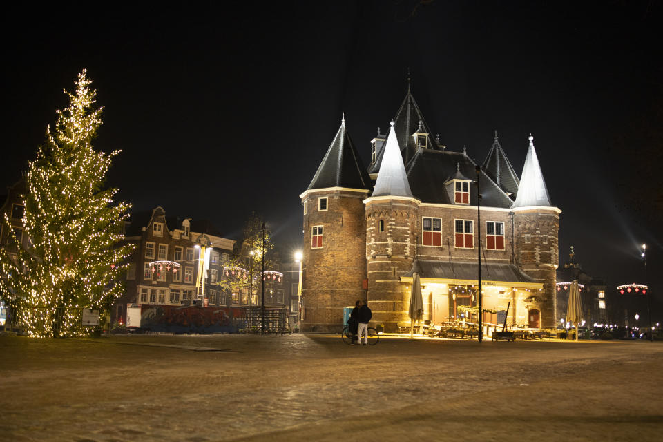 FILE- In this Thursday Dec. 31, 2020, file photo, A couple kisses on the near-deserted Nieuwmarkt square in Amsterdam, Netherlands, Thursday, Dec. 31, 2020. The Dutch government said Wednesday, Jan. 20, 2021, that it wants to impose a curfew as part of beefed-up restrictions to rein in the spread of new more contagious variants of the coronavirus that already accounts for at least one in every 10 Dutch infections.(AP Photo/Peter Dejong, File)