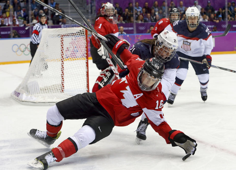 Jayna Hefford of Canada (16) loses her footing while sealing off the puck from Hilary Knight of the United States (21) during the first period of the women's gold medal ice hockey game at the 2014 Winter Olympics, Thursday, Feb. 20, 2014, in Sochi, Russia. (AP Photo/Mark Humphrey)