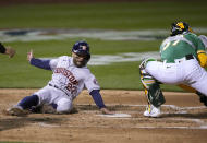 Houston Astros' Jose Altuve (27) slides into home plate to score a run past Oakland Athletics catcher Aramis Garcia (37) on a double by Michael Brantley during the fourth inning of a baseball game Friday, April 2, 2021, in Oakland, Calif. (AP Photo/Tony Avelar)