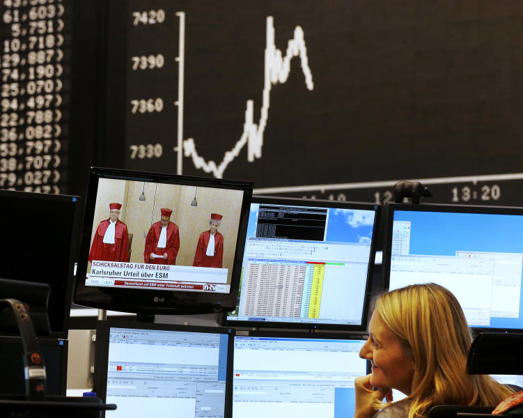A stock trader smiles as the curve of the German stock index DAX goes up as head of German Federal Constitutional Court Andreas Vosskuhle is seen on a television screen at the stock market in Frankfurt, Germany, Wednesday, Sept. 12, 2012. Germany's high court on Wednesday rejected calls to block the Europe's permanent rescue fund, paving the way in a much-anticipated ruling for its ratification by the country's president. (AP Photo/Michael Probst)