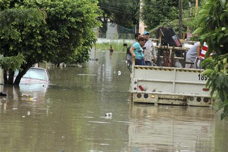 Flood-affected residents travel on the back of a truck through a flooded neighbourhood in Poza Rica
